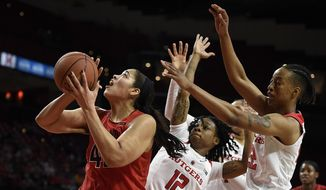 Maryland's Brionna Jones, left, shoots as Rutgers' Khadaizha Sanders, center, and Kandiss Barber defend during the first half of an NCAA college basketball game, Sunday, Jan. 22, 2017, in College Park, Md. (AP Photo/Gail Burton)