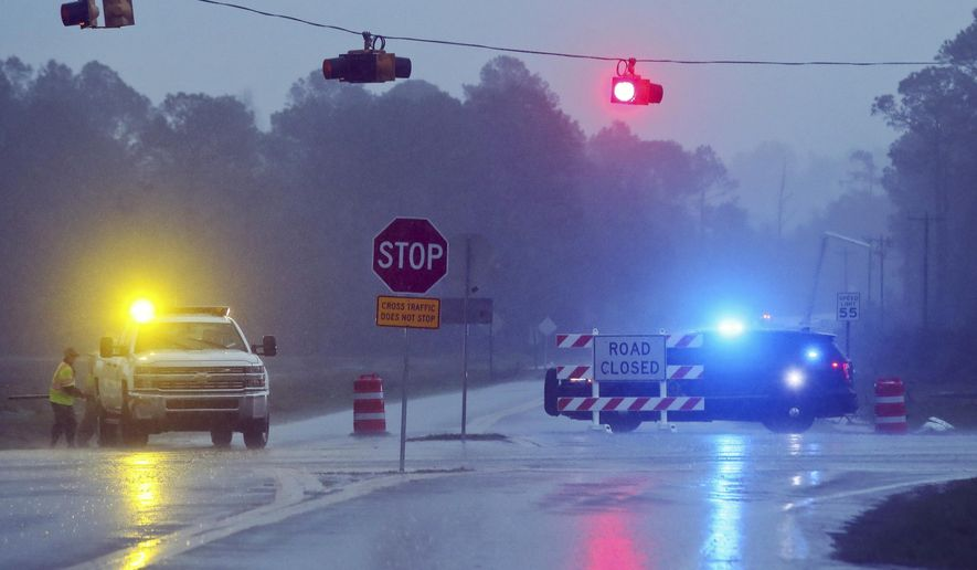 """A Brooks County Sheriff and officials block Highway 122 as power line workers repair a downed pole in the background Sunday, Jan. 22, 2017, near Barney, Ga. The National Weather Service said Sunday that southern Georgia, northern Florida and the corner of southeastern Alabama could face """"intense and long track"""" tornadoes, scattered damaging winds and large hail. (AP Photo/Phil Sears)"""