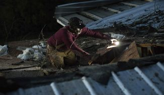 Terry Paramore works on his roof after a severe storm caused a tree to fall on his home, Sunday, Jan. 22, 2017, in Albany, Ga. Georgia Gov. Nathan Deal declared a state of emergency in several counties, including Cook, that have suffered deaths, injuries and severe damage from weekend storms. (AP Photo/Branden Camp)