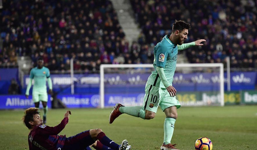 FC Barcelona's Lionel Messi, right, in action with Eibar's Takashi Inui, during the Spanish La Liga soccer match between FC Barcelona and Eibar, at Ipurua stadium in Eibar, northern Spain, Sunday, Jan. 22, 2017. (AP Photo/Alvaro Barrientos)
