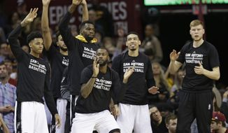 The San Antonio Spurs bench celebrates during overtime in an NBA basketball game against the Cleveland Cavaliers, Saturday, Jan. 21, 2017, in Cleveland. The Spurs won 118-115. (AP Photo/Tony Dejak)
