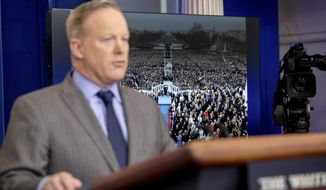 An image of the inauguration of President Donald Trump is displayed behind White House press secretary Sean Spicer as he speaks at the White House, Saturday, Jan. 21, 2017, in Washington.  (AP Photo/Andrew Harnik)