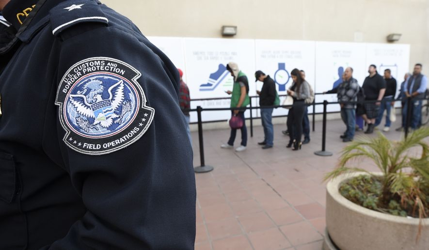 Pedestrians crossing from Mexico into the United States at the Otay Mesa Port of Entry wait in line Thursday, Dec. 10, 2015, in San Diego. (AP Photo/Denis Poroy)
