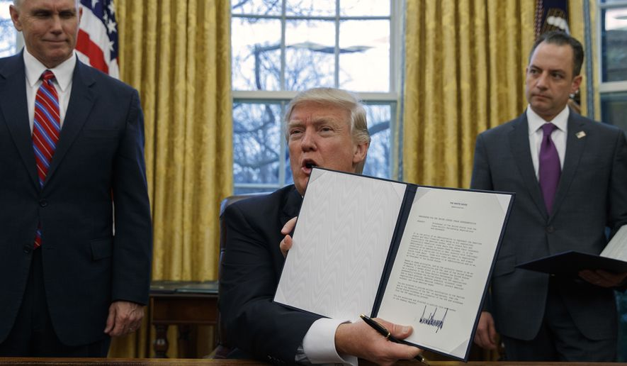Vice President Mike Pence, left, and White House Chief of Staff Reince Priebus, right, watch as President Donald Trump shows off an executive order to withdraw the U.S. from the 12-nation Trans-Pacific Partnership trade pact agreed to under the Obama administration in the Oval Office of the White House in Washington on Jan. 23, 2017. (Associated Press)