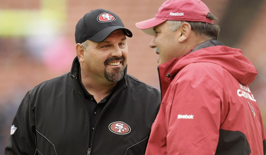 In this photo taken Jan. 2, 2011, then-San Francisco 49ers defensive coordinator Greg Manusky, left, talks with Arizona Cardinals assistant head coach Russ Grimm before an NFL football game in San Francisco. The Washington Redskins promoted Manusky to defensive coordinator and Matt Cavanaugh to offensive coordinator.  (AP Photo/Ben Margot)