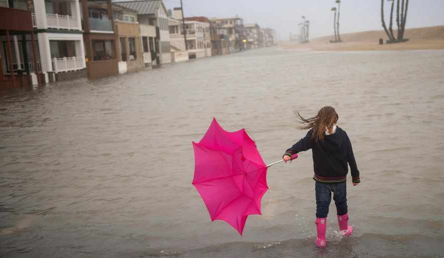Isabella Busse , 6, walks through floodwater near the Seal Beach Pier during a storm in Seal Beach, Calif., Sunday, Jan. 22, 2017. The heavy downpour on Sunday drenched Orange County in one of the heaviest storms of the year. Fast-moving floodwaters swept through California mountain communities and residents fled homes below hillsides scarred by wildfires as the third in the latest series of storms brought a deluge Sunday and warnings about damaging mudslides. (Ana Venegas/The Orange County Register via AP)