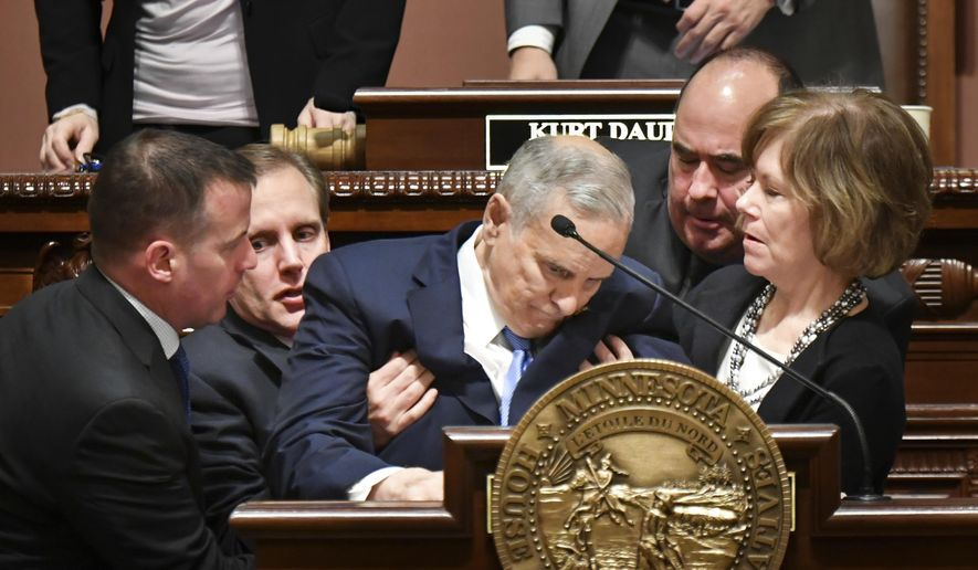 """Minnesota Lt. Governor Tina Smith, right, and Secretary of State Steve Simon, left, help Minnesota Gov. Mark Dayton after he collapsed during his State of the State address in St. Paul, Minn., Monday, Jan. 23, 2017. House Speaker Kurt Daudt said minutes after the incident that Dayton was """"up and about"""" and that the governor would be OK. (Glen Stubbe/Star Tribune via AP)"""