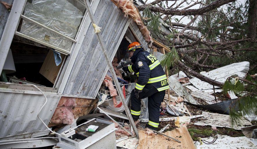 A rescue worker enters a hole in the back of a mobile home Monday, Jan. 23, 2017, in Big Pine Estates that was damaged by a tornado, in Albany, Ga. Fire and rescue crews were searching through the debris, looking for people who might have become trapped when the deadly storm came through. (AP Photo/Branden Camp)