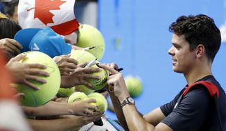 Canada's Milos Raonic signs autographs after defeating Spain's Roberto Bautista Agut in their fourth round match at the Australian Open tennis championships in Melbourne, Australia, Monday, Jan. 23, 2017. (AP Photo/Dita Alangkara)