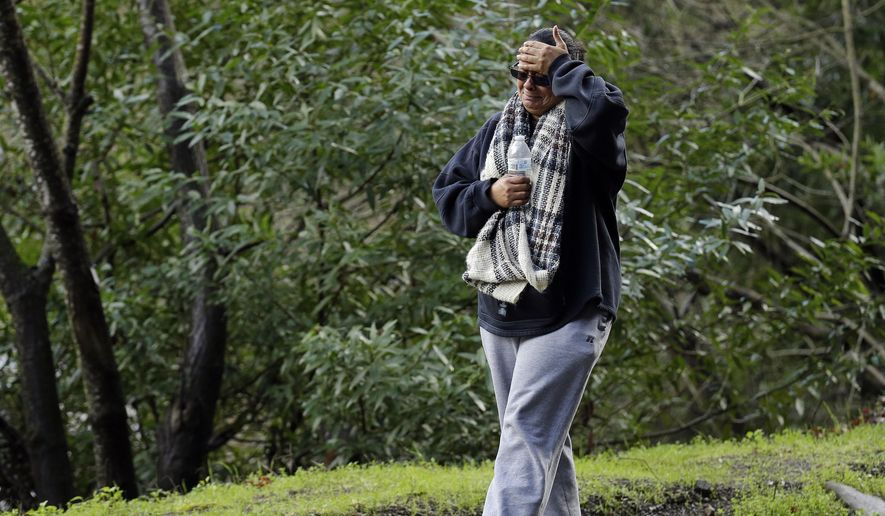 The mother of a missing 18-year-old woman places her hand to her head after viewing the scene where her daughter's car careened off the road Monday, Jan. 23, 2017, on Niles Canyon Road near Fremont, Calif. The unidentified woman's car plunged into rushing waters after colliding with another vehicle on Saturday and is suspected as being in the submerged vehicle. (AP Photo/Ben Margot)