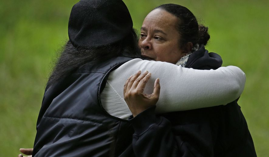 The mother of a missing 18-year-old woman, right, receives a hug near the scene where her daughter's car lies submerged in Alameda Creek on Monday, Jan. 23, 2017, on Niles Canyon Road near Fremont, Calif. The unidentified woman's car plunged into rushing waters after colliding with another vehicle on Saturday, Jan. 21, 2017, and she is suspected as being in the submerged vehicle. (AP Photo/Ben Margot)