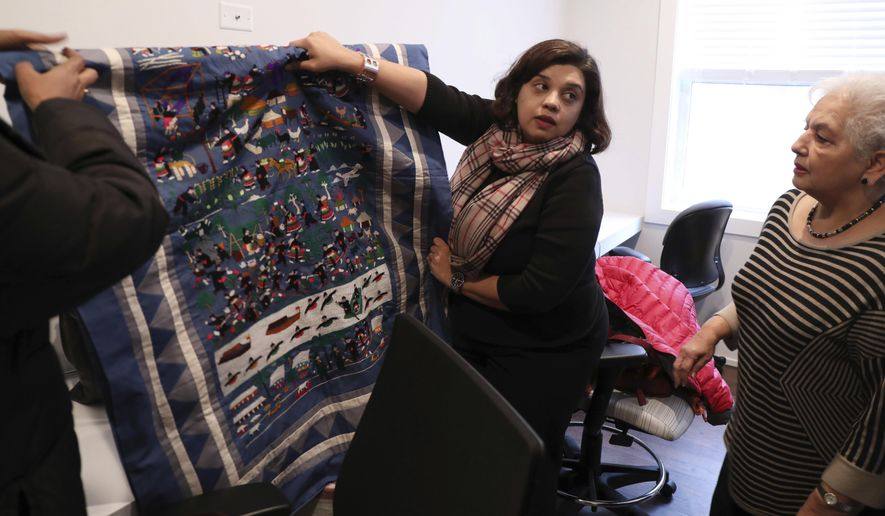 In a Wednesday, Jan. 18, 2017 photo, Neha Gill, center, executive director of Apna Ghar, and board member Usha Wasan, right, hang woven art at the shelter's new 12-bedroom site in Chicago's Uptown neighborhood. The shelter, specializing in issues facing Asian immigrants, is planning the opening of a new $1.25 million, 12-bedroom facility, one of the largest of its kind in the nation. (Phil Velasquez/Chicago Tribune via AP)