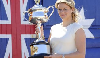 FILE - In this Jan. 30, 2011, file photo, Belgium's Kim Clijsters poses for photographers with her Australian Open trophy at Melbourne's Brighton Beach, Australia. Clijsters and Andy Roddick have been elected to the International Tennis Hall of Fame. (AP Photo/Andrew Brownbill, File)