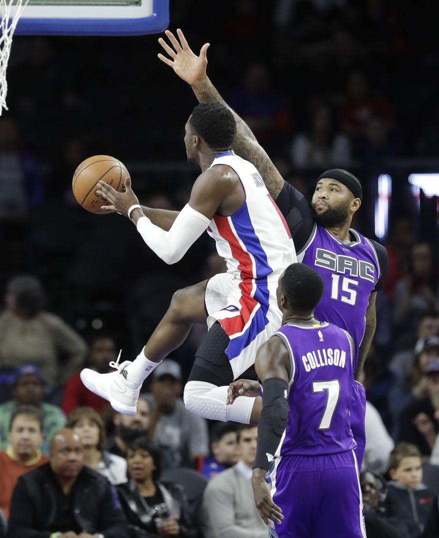 Detroit Pistons guard Reggie Jackson (1) makes a layup defendd by Sacramento Kings forward DeMarcus Cousins (15) during the first half of an NBA basketball game, Monday, Jan. 23, 2017, in Auburn Hills, Mich. (AP Photo/Carlos Osorio)