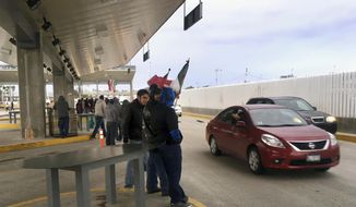 Protesters in Tijuana, Mexico, wave through motorists at the Otay Mesa Port of Entry with San Diego, Calif., after Mexican authorities abandoned their posts on Sunday, Jan. 22, 2017. Protesters took control of vehicle lanes at one of the busiest crossings on the U.S. border Sunday to oppose Mexican gasoline price hikes, waving through motorists into Mexico after Mexican authorities abandoned their posts. (AP Photo/Elliot Spagat)