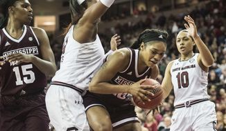 Mississippi State forward Victoria Vivians, second from right, with teammate Teaira McCowan (15), drives to the hoop against South Carolina center Alaina Coates, second from left, and Allisha Gray (10) during the first half of an NCAA college basketball game, Monday, Jan. 23, 2017, in Columbia, S.C. (AP Photo/Sean Rayford)