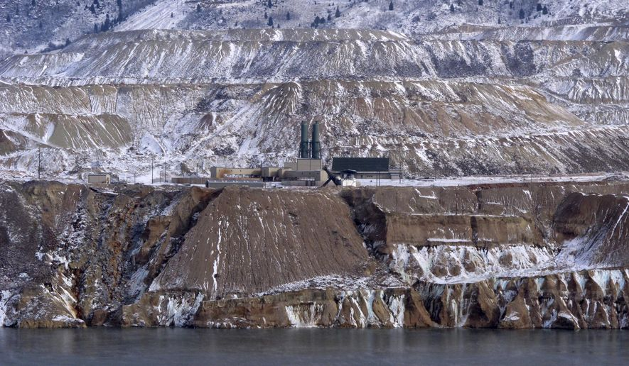 In this Dec. 14, 2016, photo the Horseshoe Bend Treatment Plant is seen at the far shore of the Berkeley Pit in Butte, Mont. Federal officials plan to pump the toxic water into the plant starting in 2023 to keep it below a critical level and prevent it from escaping the pit. (AP Photo/Matt Volz)