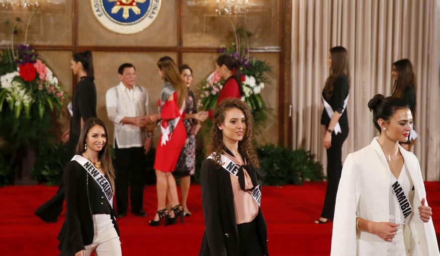 Miss Universe contestants, from left in foreground, Tania Dawson of New Zealand, Zoey Ivory of The Netherlands and Lizelle Esterhuizen of Namibia, walk back to their seats after posing with Philippine President Rodrigo Duterte, second from left in background, during their courtesy call at Malacanang Palace Monday, Jan. 23, 2017 in Manila, Philippines. Eighty-six candidate are vying for the title in the grand coronation Jan.30 to succeed Pia Wurtzbach of the Philippines. (AP Photo/Bullit Marquez)