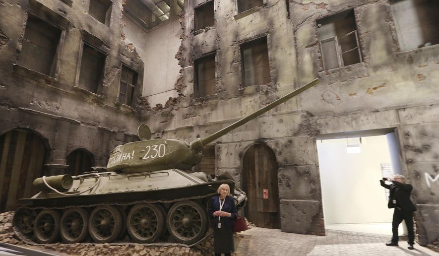 A woman stands in front of an exhibit in the Museum of the Second World War, an ambitious new museum under creation for nine years has opened its doors for a day to historians, museums and reporters in Gdansk, Poland, on Monday, Jan. 23, 2017.  (AP Photo/Czarek Sokolowski)