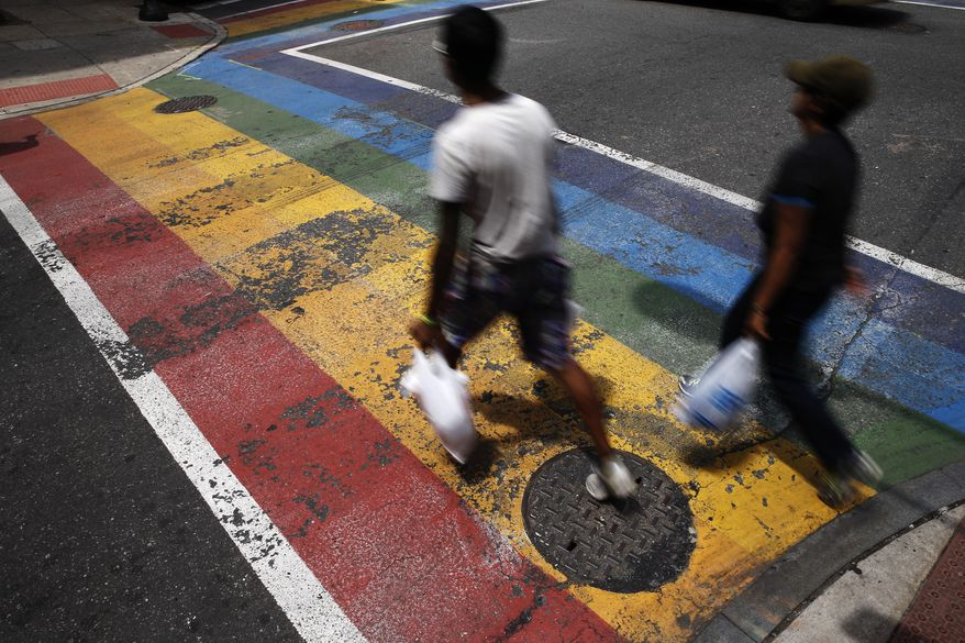In this June 17, 2016, file photo, people walk across a rainbow crosswalk painted in support of the LGBT community in the Gayborhood, a gay-friendly section of Philadelphia. The Philadelphia Commission on Human Relations recommended Monday, Jan. 23, 2017, that bars and nonprofit organizations in Philadelphia's gay neighborhood undergo training for racial bias and hire more diverse staff, after a new city report found women, minorities and transgender people have felt unwelcome and unsafe in the Gayborhood for decades. (AP Photo/Matt Rourke, File)
