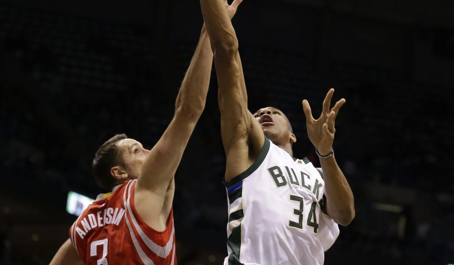 Milwaukee Bucks' Giannis Antetokounmpo, right, shoots against the Houston Rockets' Ryan Anderson (3) during the second half of an NBA basketball game Monday, Jan. 23, 2017, in Milwaukee. (AP Photo/Jeffrey Phelps)