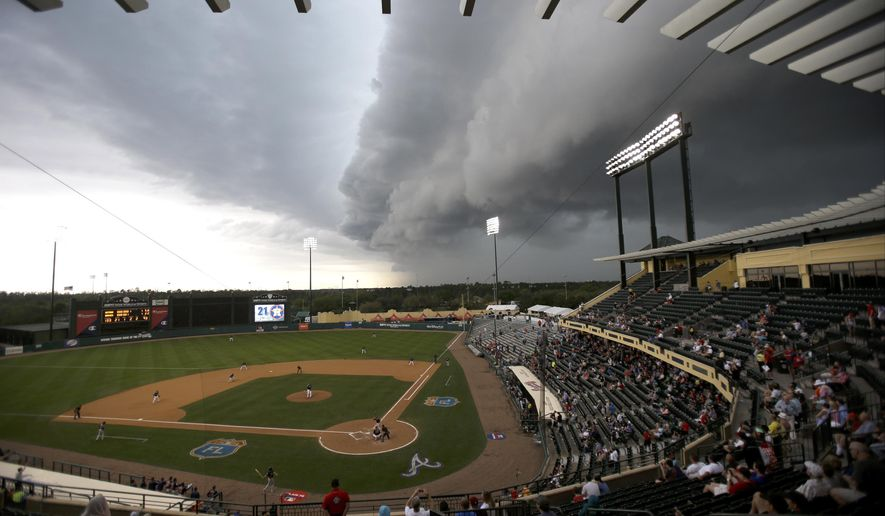 FILE - This March 25, 2016 file photo shows storm clouds rolling in over Champion Stadium in the seventh inning of a spring training baseball game between the Atlanta Braves and the Houston Astros in Kissimmee, Fla. Spring training will be shortened by two days starting in 2018, when new restrictions in Major League Baseball's collective bargaining agreement take effect on game times for regular-season getaway days. (AP Photo/John Raoux, file)
