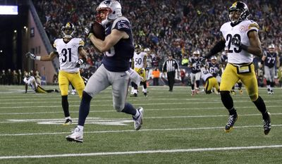 New England Patriots wide receiver Chris Hogan (15) makes a touchdown reception between Pittsburgh Steelers defenders Ross Cockrell (31) and Mike Mitchell (23) during the first half of the AFC championship NFL football game, Sunday, Jan. 22, 2017, in Foxborough, Mass. (AP Photo/Charles Krupa)