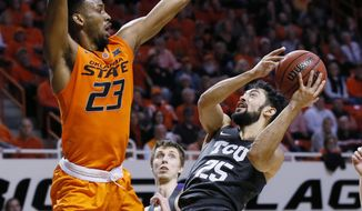 TCU guard Alex Robinson (25) shoots as Oklahoma State forward Leyton Hammonds (23) defends in the second half of an NCAA college basketball game in Stillwater, Okla., Monday, Jan. 23, 2017. Oklahoma State won 89-76. (AP Photo/Sue Ogrocki)