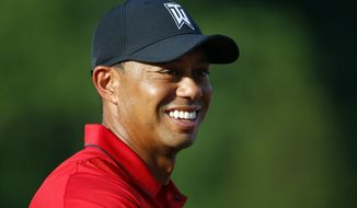 FILE - In this June 26, 2016, file photo, Tiger Woods stands on the 18th green during the trophy ceremony for Quicken Loans National PGA golf tournament winner Billy Hurley III in Bethesda, Md. Woods discusses his impending return to Riviera for the Genesis Open in February, the hometown tournament that golf's aging superstar has skipped since 2006. Despite his love for the venerable course, Woods has never won there. (AP Photo/Patrick Semansky, File)