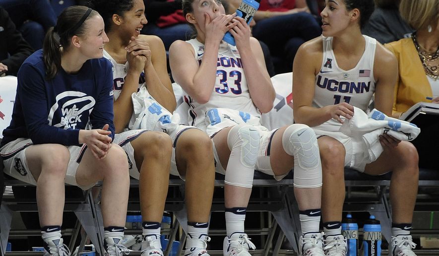 Connecticut's Katie Lou Samuelson (33) teases teammate Gabby Williams, second from left, as Tierney Lawlor, left, and Kia Williams, right, watch in the second half of an NCAA college basketball game against Tulane, Sunday, Jan. 22, 2017, in Storrs, Conn. Williams took an elbow to her tooth in an earlier play. (AP Photo/Jessica Hill)
