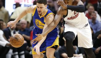 Golden State Warriors guard Klay Thompson, left, and Miami Heat center Hassan Whiteside (21) battle for a loose ball during the first half of an NBA basketball game, Monday, Jan. 23, 2017, in Miami. (AP Photo/Wilfredo Lee)
