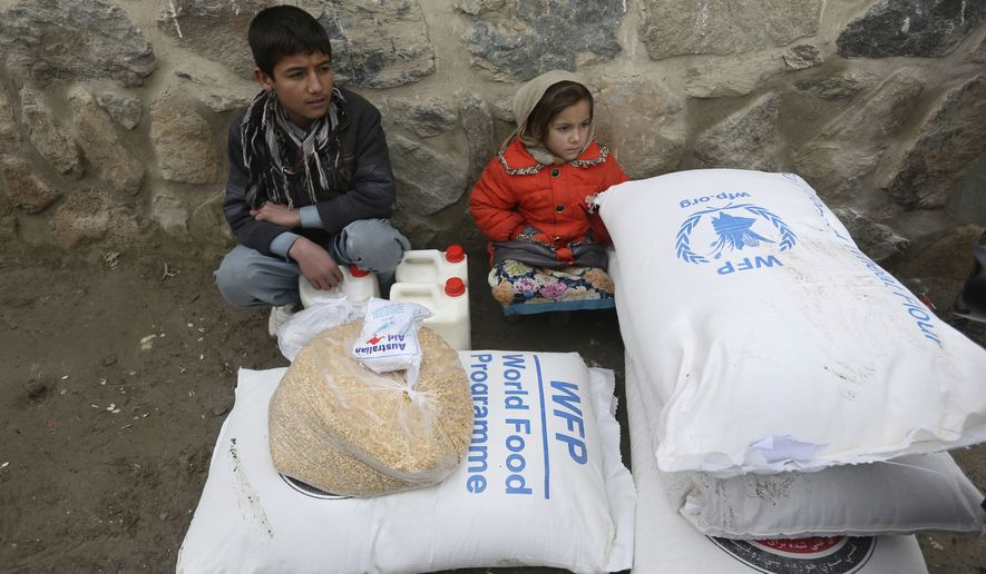 Children wait for transportation after receiving food donated by the World Food Program, in Kabul, Afghanistan, Tuesday, Jan. 24, 2017. (AP Photo/Rahmat Gul)