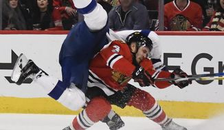 Tampa Bay Lightning center Brian Boyle flips over as he collides with Chicago Blackhawks defenseman Niklas Hjalmarsson (4) after scoring a goal during the first period of an NHL hockey game Tuesday, Jan. 24, 2017, in Chicago. (AP Photo/Matt Marton)