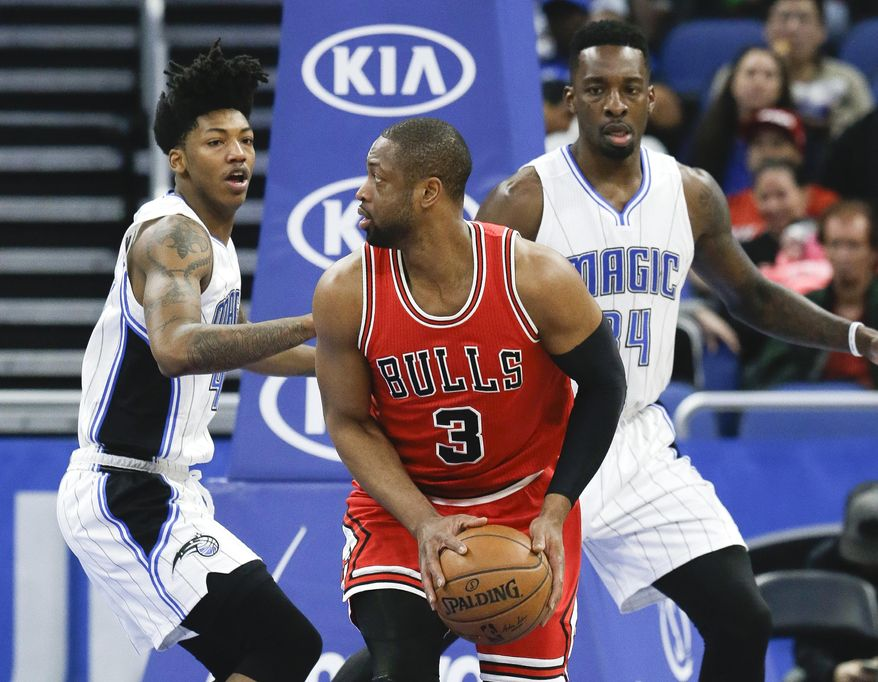 Chicago Bulls' Dwyane Wade (3) looks fort a shot against Orlando Magic's Elfrid Payton, left, and Jeff Green, right, during the first half of an NBA basketball game, Tuesday, Jan. 24, 2017, in Orlando, Fla. (AP Photo/John Raoux)