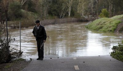 Dennis Rogers stands next to a flooded trail along Los Gatos Creek after a series of storms Tuesday, Jan. 24, 2017, in Los Gatos, Calif. (AP Photo/Marcio Jose Sanchez)