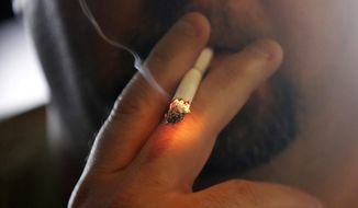 In this April 21, 2015, file photo, a man smokes a cigarette in New Orleans. (AP Photo/Gerald Herbert) **FILE**