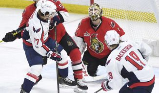 Ottawa Senators goalie Mike Condon (1) keeps an eye on the puck while defenceman Cody Ceci (5) defends against Washington Capitals right wing T.J. Oshie (77) and centre Nicklas Backstrom (19) during third period of NHL hockey action in Ottawa on Tuesday, Jan. 24, 2017. (Sean Kilpatrick/The Canadian Press via AP)