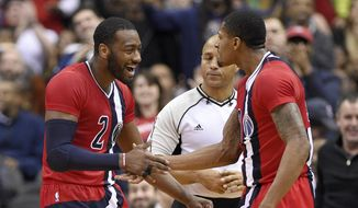 Washington Wizards guard John Wall (2) smiles at guard Bradley Beal, right, after Beal was fouled on a shot during the second half of an NBA basketball game against the Boston Celtics, Tuesday, Jan. 24, 2017, in Washington. The Wizards won 123-108. (AP Photo/Nick Wass)