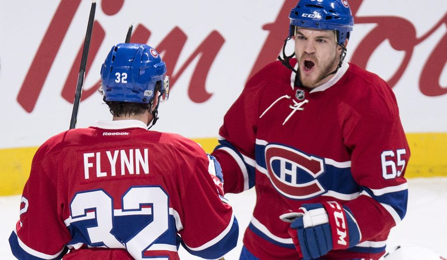 Montreal Canadiens center Andrew Shaw (65) celebrates his goal with teammate center Brian Flynn (32) as they face the Calgary Flames during the first period of an NHL hockey game in Montreal on Tuesday, Jan. 24, 2017. (Paul Chiasson/The Canadian Press via AP)