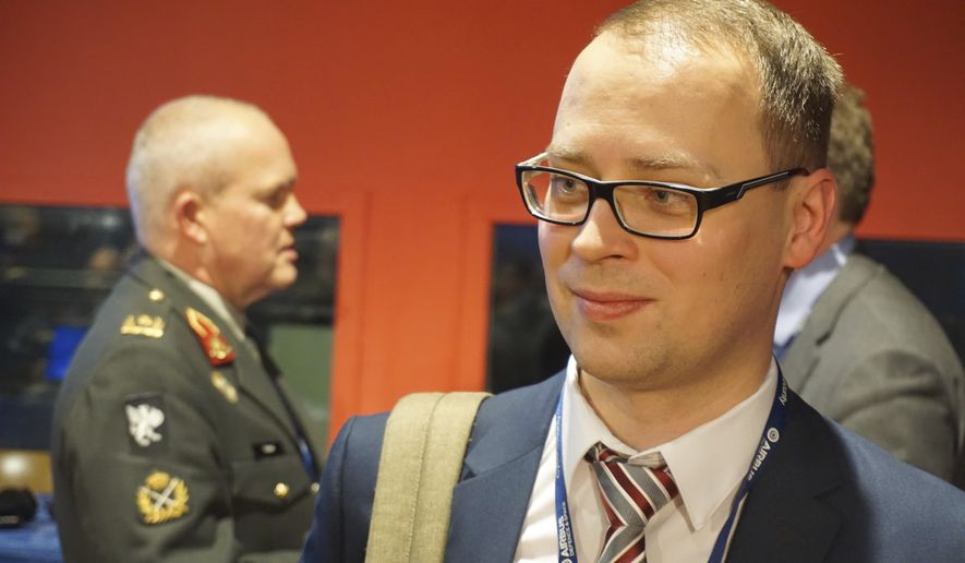 Estonian defense official Erki Kodar chats with a conference goer as part of a Cyber Security conference held in Lille, northern France, Tuesday, Jan. 24, 2017. Estonia is experimenting with the idea of cyberconscription, giving draftees with tech skills the chance to step into roles defending the military's electronic infrastructure. (AP Photo/Raphael Satter)