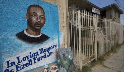 FILE - In this July 6, 2015, file photo, a mural and memorial for the late Ezell Ford Jr., who was fatally shot by Los Angeles police officers is seen in South Los Angeles. Two Los Angeles police officers acted in self-defense when they fatally shot the 25-year-old black man during a struggle over an officer's gun and will not face criminal charges for the 2014 shooting that led to protests, prosecutors said Tuesday, Jan. 24, 2017. (AP Photo/Damian Dovarganes, File)