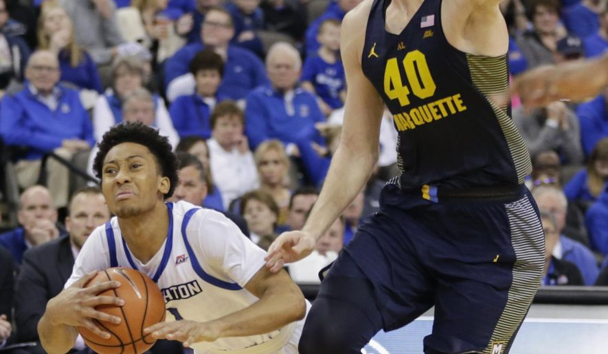 Creighton's Davion Mintz (1) falls while trying to get around Marquette's Luke Fischer (40) during the second half of an NCAA college basketball game in Omaha, Neb., Saturday, Jan. 21, 2017. Marquette won 102-94. (AP Photo/Nati Harnik)