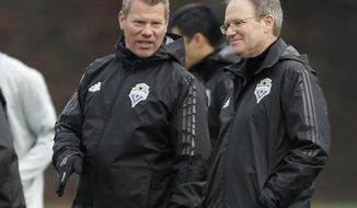 Seattle Sounders head coach Brian Schmetzer, right, talks with David Tenney, left, manager of performance and sports science, during the first training session of the 2017 MLS soccer season, Tuesday, Jan. 24, 2017, in Tukwila, Wash. (AP Photo/Ted S. Warren)
