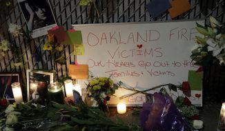 """FILE - In this Monday, Dec. 5, 2016, file photo, candles, photos and flowers are placed at a makeshift memorial near the site of a massive warehouse fire in Oakland, Calif. Micah Allison, the wife of the founder of a ramshackle Oakland artists' colony where dozens of people burned to death in a fire last month says she's sorry about what happened but is angry about what she called """"pretty terrible"""" treatment by the media and ex-neighbors. (AP Photo/Marcio Jose Sanchez, File)"""
