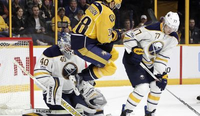 Nashville Predators left wing Viktor Arvidsson (38), of Sweden, jumps out of the way of a shot as Buffalo Sabres goalie Robin Lehner (40), of Sweden, and defenseman Dmitry Kulikov (77), of Russia, guard the net during the second period of an NHL hockey game, Tuesday, Jan. 24, 2017, in Nashville, Tenn. (AP Photo/Mark Humphrey)