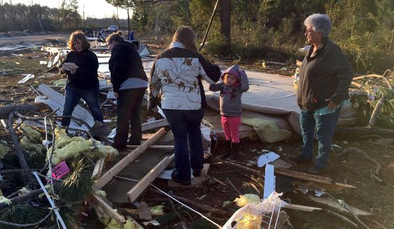 Bonnie Collier, right, and her two granddaughters, daughter and daughter-in-law pick through the wreckage of her mobile home trying to find clothes and family photos on Monday, Jan. 23, 2017, near Cecil, Ga. (AP Photo/Brendan Farrington)
