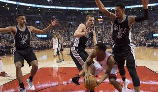 Toronto Raptors guard Kyle Lowry (7) looks to pass under heavy pressure from San Antonio Spurs guard Kyle Anderson (1), forward David Lee (10) and guard Danny Green (14) during the first half of an NBA basketball game Tuesday, Jan. 24, 2017, in Toronto. (Frank Gunn/The Canadian Press via AP)