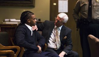 Attorney Bill Massey, right, touches his client, Treveno Campbell, during the first day of his murder trial Tuesday, Jan. 24, 2017, at the Shelby County Criminal Justice Center in Memphis, Tenn. Campbell is charged with killing Memphis police officer Martoiya Lang in 2011. (Yalonda M. James/The Commercial Appeal via AP)