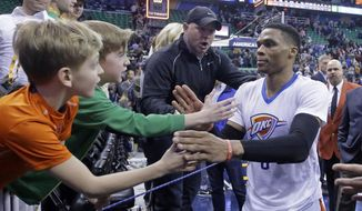 Fans reach for Oklahoma City Thunder guard Russell Westbrook (0) as he leaves the court following their NBA basketball game against the Utah Jazz on Monday, Jan. 23, 2017, in Salt Lake City. The Thunder won 97-95. (AP Photo/Rick Bowmer)