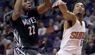 Minnesota Timberwolves forward Andrew Wiggins (22) shoots over Phoenix Suns forward TJ Warren (12) during the first half of an NBA basketball game, Tuesday, Jan. 24, 2017, in Phoenix. (AP Photo/Matt York)